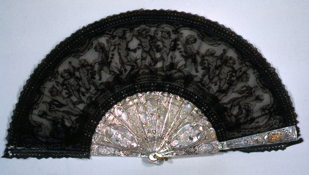 Pleated fan with a black bobbin-made Chantilly lace leaf decorated with a line of dancing putti carrying a floral garland. The sticks are carved and gilded mother-of-pearl, decorated with oval medallions of putti. On each guard stick is a medallion with the initials FB.