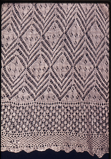 Large, loose overblouse of patterned knitted lace. Trimmed at standing collar and cuffs of long sleeves with machine lace edging. Possibly a surplice.