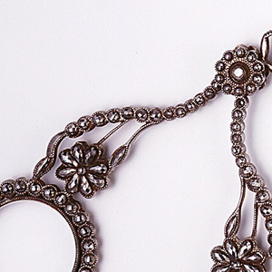 The glasses, each set at the end of a flowering stem, hinged together with ring at hinge. (b) Chain of oval links of steel.