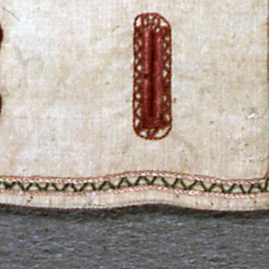 Small sampler with eight rectangular button holes in blue, green, yellow and pink, and eight eyelets in red.  In the center, a monogram with a crown above. Green zigzag border. On off-white linen.