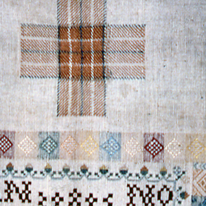 Central square with inner borders surrounded by darning crosses and squares of embroidery.  Square at upper left unfinished.