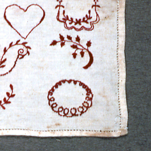Alphabets at top; monograms and motifs at bottom, all in red on white. Marking sampler