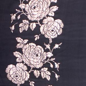 Black ground with gold brocaded design. Three vertically-running serpentine columns of roses. Both selvedges present.