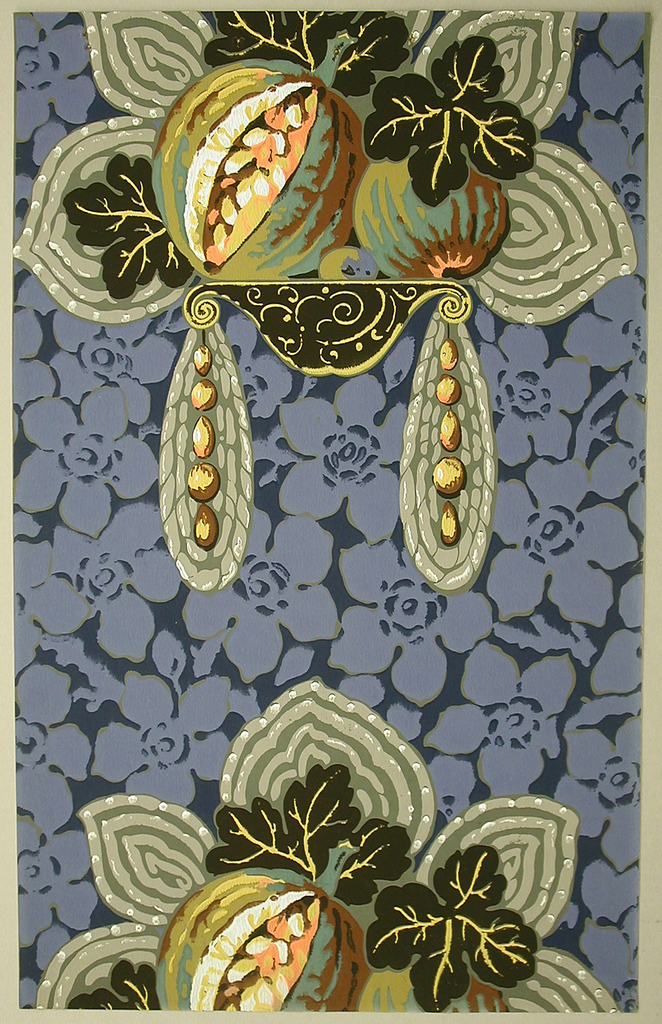 Repeating pattern of two large pieces of exotic fruit with large, flower-shaped leaves, sitting on a narrow shelf. Behind the fruit is a silver decoration in the shape of five leaves. Hanging from either end of the shelf are two silver pendants with gold beads running vertically down the center of each. The background has a large, flat, floral motif in a light blue with a darker blue background. The fruits are yellow, turquoise, and orange.