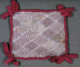 Diamond grid with patterns.  Mounted on red silk, red woven tape bows at each corner.
