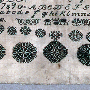 Horizontal sampler with alphabets and numerals at the top, followed by pattern bands and circular medallions, all in black on an unbleached ground.