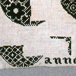 Black on natural.  Alphabets at top.  Unfinished pattern circles at bottom.