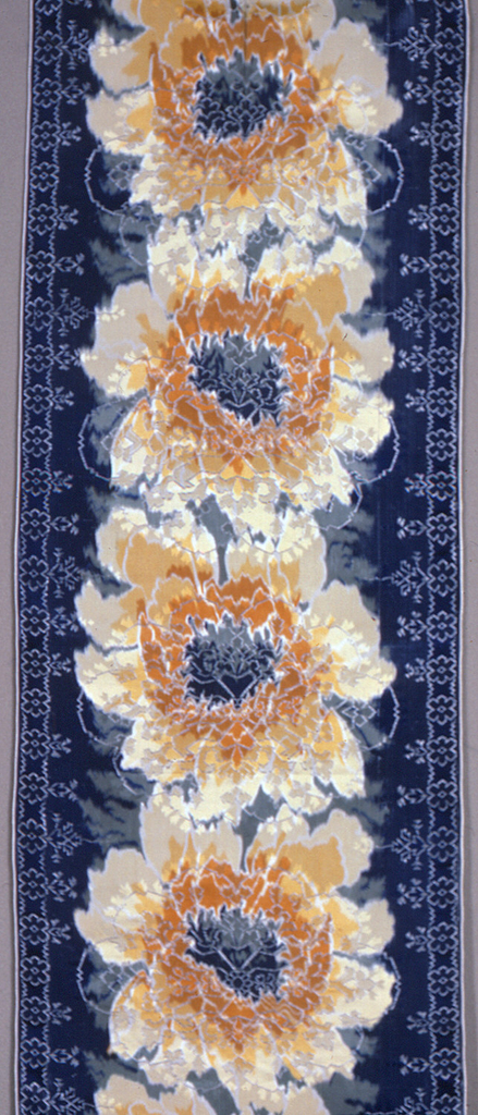 Chiné-printed ribbon has large-scale overlapping vertical blossoms in yellow-orange and white on a dark blue ground. Over these blossoms are woven stylized symmetrical floral forms and small-scale rosettes that create narrow side borders.
