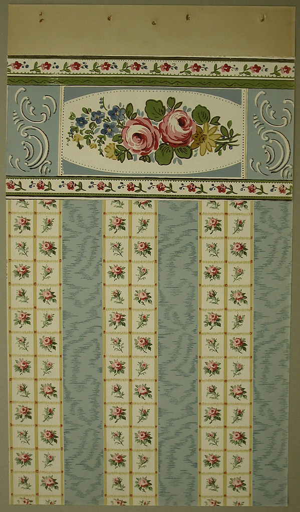 The center contains  two pink roses and other, smaller flowers contained within a  a white oval, which is cut off by a rectangular frame. On each side of the frame are white, rococo-inspired tendrils. Along the top of the border is line of small prink flowers and blue buds with a white background. Below this is another vertically stripe in green with a thin, indulating brown line. The bottom of teh border contains the same line of pink flowers. The background of the middle section is a soft blue.
