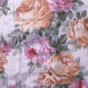 White moiré ground with an allover chiné pattern of large-scale pink and yellow roses. Both selvedges present.