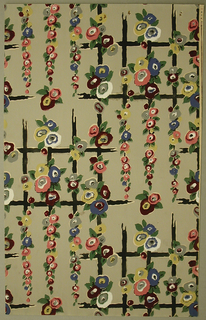 Art Deco sidewall with all-over design of rectilinear black lattice decorated with hanging clusters of flowers; rectangular repeat in off-set columns; flowers formed from concentric blobs of white and pink, dark red, yellow, or blue with small green leaves at their edges; lattice has gaps in places as if rotted away; muted yellow-green ground.