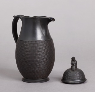 Tall, slightly swelling body, long loop handle, short spout; high domed lid with finial in the form of a draped female figure.  Sides of body (lower portion) and lid with basket-weave texture; wide band top section of body plain.