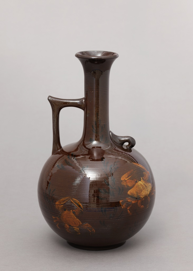 Jug or ewer consisting of a thrown red clay body. The spherical body is surmounted with a long cylindrical neck and a flaring lip. Prominent concentric ridges around body and neck, in the clay.  Squared handle applied at the shoulder on one side and small curved hook on the other.  Body decorated with three large crabs in yellow and white underglaze slip.  Suggestions of plant life in dark brown slip.  Against mahogany ground various aventurine effects in the yellow glaze.