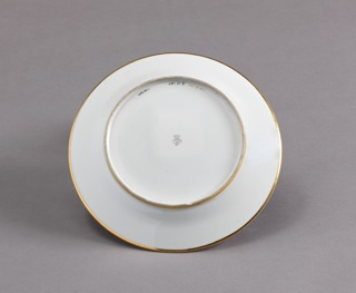 """Circular plate. In center, a polychromed scene of barrel washing, """"Brasserie"""" above """"Entonnerie."""" beneath, gilt rim with deep blue diaper pattern."""