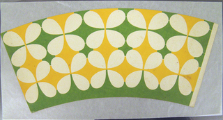 Off-white four-petal flowers on a bright green and yellow ground in two registers across the sheet. The flowers conform to the shape of the sheet.  This example shows the cup at a stage prior to its pre-waxing and factory construction into a circular cup.