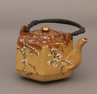 Paneled octagonal body with short curved spout and circular lid with flattened knob finial.  Attached to posts on shoulder is bronze bail-like handle in form of two dolphins rising upward.  Low-relief underglaze decoration on front and back of prunus sprigs in white, blue-gray and brown slips on the ginger ground.  Shoulder and top painted burnt-siena.  Gilt accents on the top, spout and two of the sides.  Bottom and interior glazed.