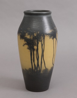 White clay body, thrown.  Ovoid body with a gradual taper from shoulder to rim, thick lip; no foot.  Decorated with tall slender trees and branches.  Underbrush covering lower third of body and tree foliage filling third to lip.  Trees and foliage in dark brown underglazed slip against ivory background.  Interior is greenish-white, glazed.  Allover vellum glaze, crackled.  Bottom glazed.