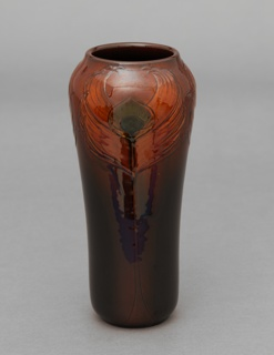 "Red clay body, cast.  Cylindrical body swelling at shoulder with slightly raised rim; no foot.  Incised decoration of three upright peacock feathers with green ""eyes"" encircle the shoulder, stems extend to base; very stylized.  Body shading from dark brown to burnt-orange at shoulder.  Allover orange glaze with fine aventurine effects.  Bottom glazed; foot rim not glazed."