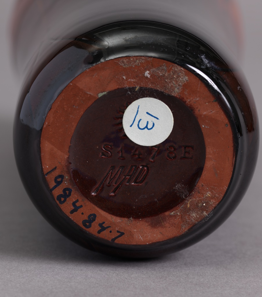 """Red clay body, cast.  Cylindrical body swelling at shoulder with slightly raised rim; no foot.  Incised decoration of three upright peacock feathers with green """"eyes"""" encircle the shoulder, stems extend to base; very stylized.  Body shading from dark brown to burnt-orange at shoulder.  Allover orange glaze with fine aventurine effects.  Bottom glazed; foot rim not glazed."""