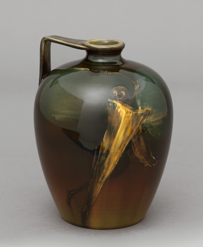 Thrown gray-green earthenware body; applied handle, decorated with ghostly figure of a skeleton in a shroud, one arm upraised and holding a burning lamp. Figure in shades of ocher, pale brown, dark brown, and green. Background shaded in ochers, browns, and dark green. Yellow graze wih aventurine effects.