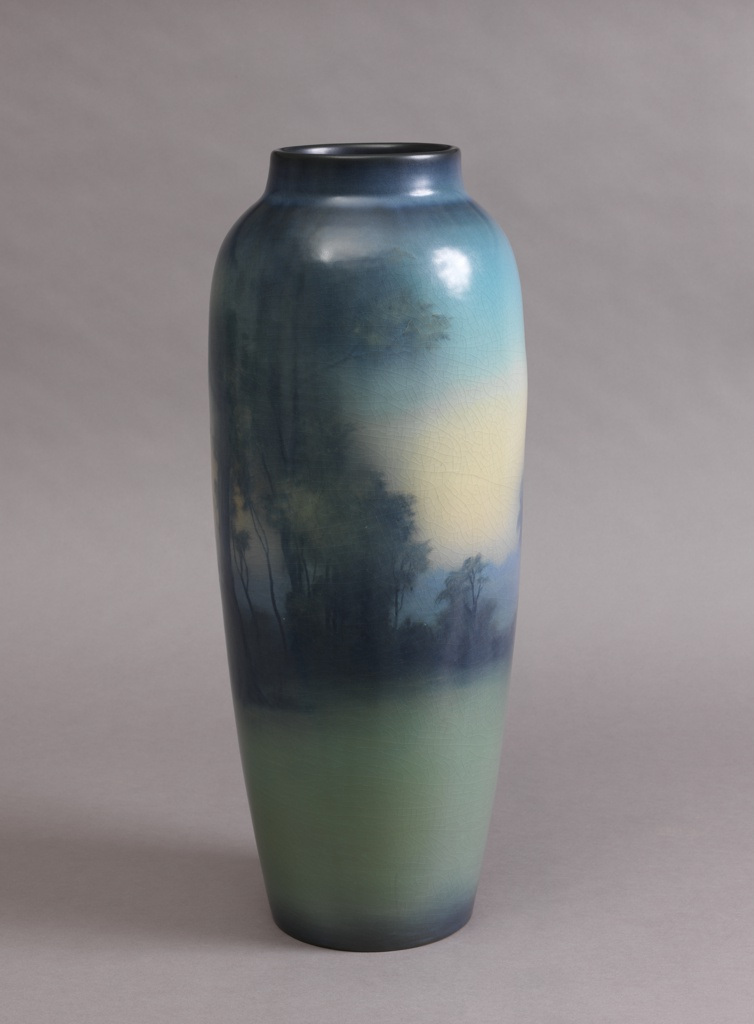 White clay body, thrown.  Elongated-ovoid cylindrical body with short raised neck; no foot.  Underglaze slip decorated all around body with landscape scene: trees and brush in foreground; lake in middle ground, and trees in low hills in background.  Predominantly blues and greens, sky shading to pale yellow and peach.  Lower body is light green.  Allover vellum glaze; crackle.  Interior and bottom glazed.