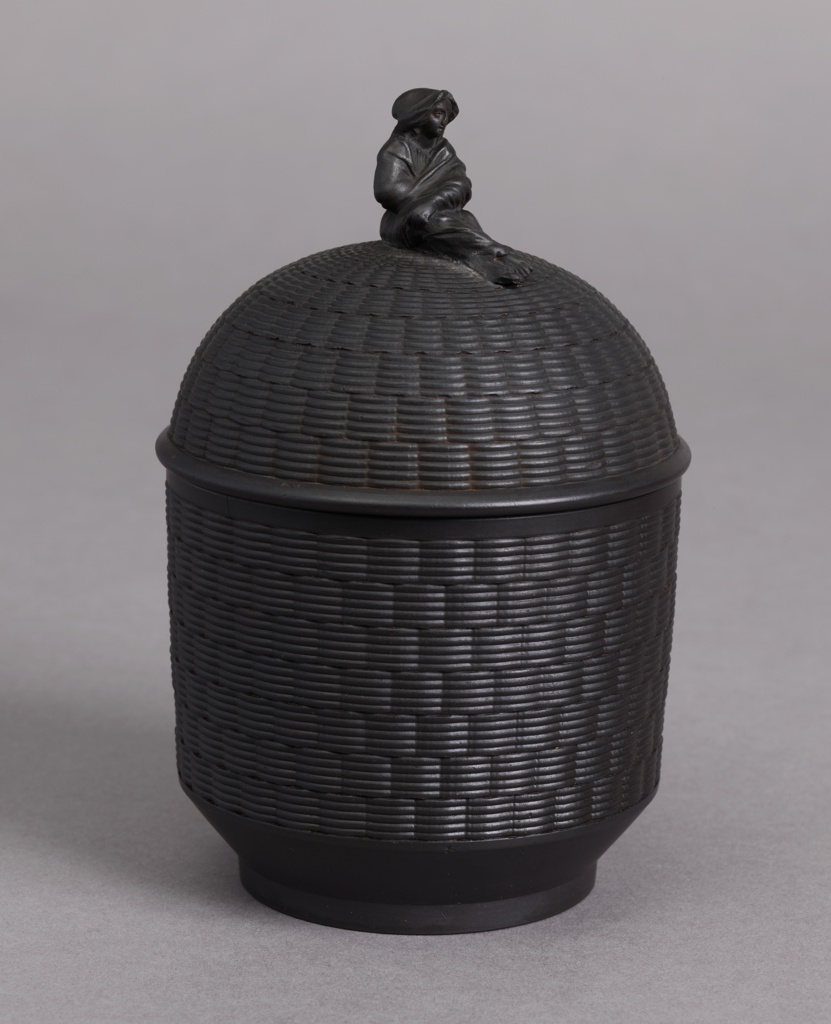 Cylindrical, high domed lid with finial in the form of a draped female figure; basket-weave texture sides and lid.