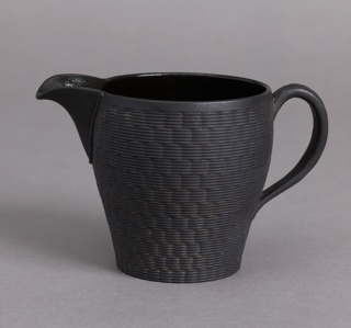 Slightly swelling form, short spout, long loop handle; sides with basket-weave texture.