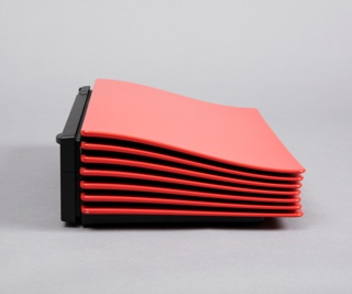 Bright red minimal rectangular form; slightly undulating top panel and accordion-like vents visible from three sides; low, black rectangular base.