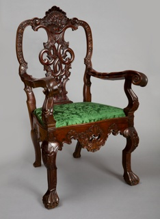 Elaborately carved mahogany or primavera chair inspired by Chippendale design; the upholstery is modern.