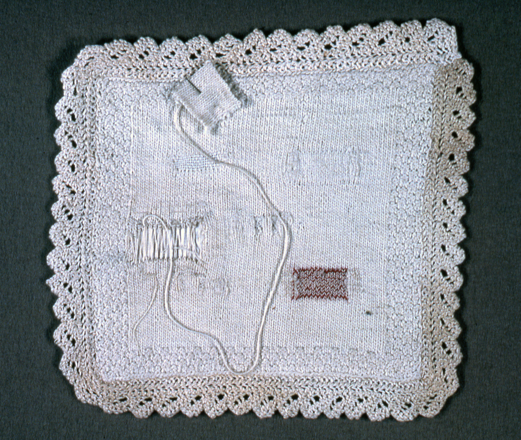Small square of knitting in white cotton with knitted lace edging on all four sides. Squares are cut from field in the manner of a darning sampler, and filled. Unfinished. The square which has been removed is attached with a pin.