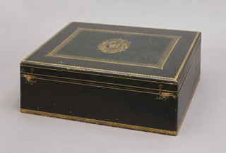 """Rectangular box (a) covered in dark green leather with stamped gilt bands and borders; hinged lid decorated with gilt borders and a cartouch comprising a crown surmounting flowing ribbons and drapery surrounding an eagle encircled by a chain of office(?) with the letter """"N"""" in shield, and pendant medal.  Two hook closures at front.  Interior lined in tan suede and fabric, with wells for cabaret service pieces; rectangular suede cushion (b)."""