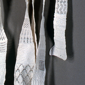 Very long narrow sampler with 106 knitted patterns in white cotton.