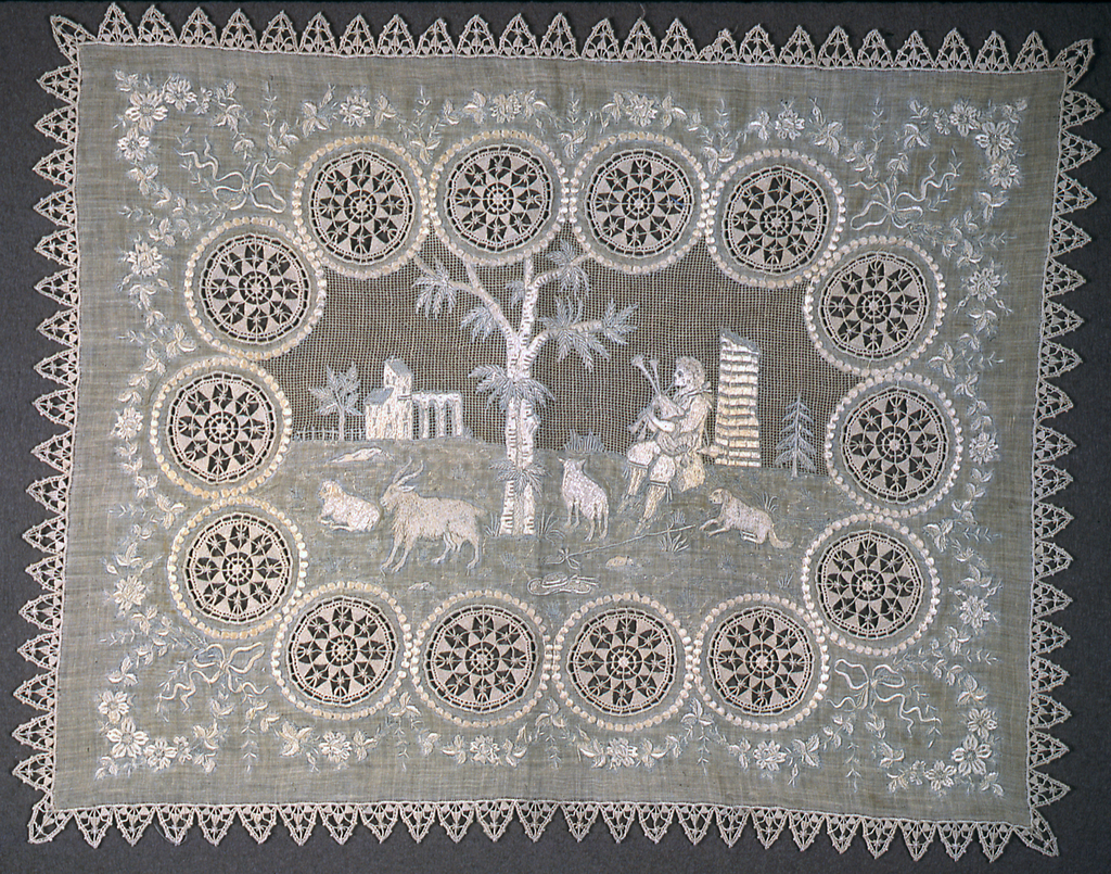 White rectangular table mat with machine-embroidered picture of a shepherd in a pastoral landscape, surrounded by floral medallions, floral garlands, and a border of needle lace.