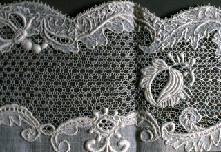 Plain white square with lace border with different mesh ground every three inches.