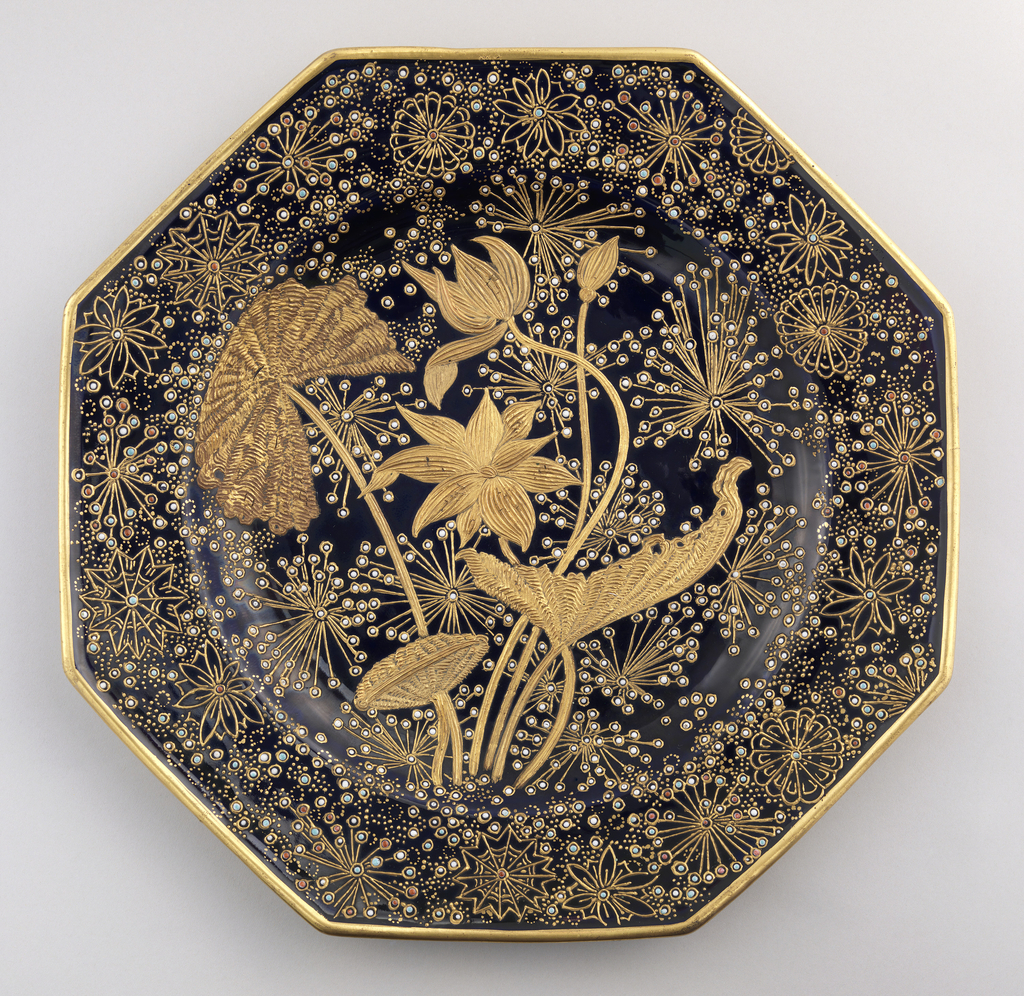 Octagonal shape with gold-banded edge.  Heavily guilded, incised water plants in center, with space-filling floral and leaf forms of gold, with enamel color dots and smaller gold dots.  Porcelain with blue underglaze decoration and overglaze enamelling and gilding.