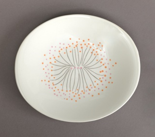 Oval plate decorated with stylized sunburst pattern of black lines with pink and orange dots on a white ground..