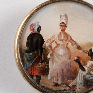 Button depicting scene of three women in a landscape, with large house in background. A standing bare-breasted dark-skinned woman holding a basket of items and another seated woman wearing striped pants, selling fruit, flank an elegantly-dressed light-skinned woman wearing a corseted gown with peach sleeves and large gold earrings.