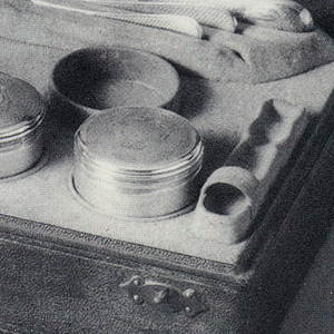 Set consisting of cylindrical silver coffeepot with straight ivory handle projecting from side; circular lid with ivory knop;  cylindrical stand;  burner;  two covered cannisters; knife, 2 spoons. All in a retangular fitted leather case with the initials BM on the hinged lid.