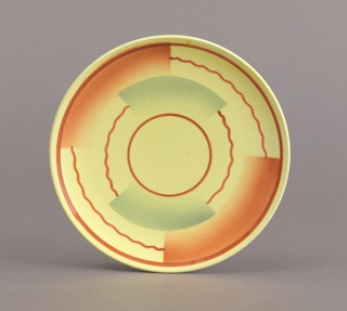 Circular plate with up-curved rim; decoration of yellow ground with straight and wavy brown lines forming concentric circles broken by semi-rectangular airbrushed swatches of brown and green.
