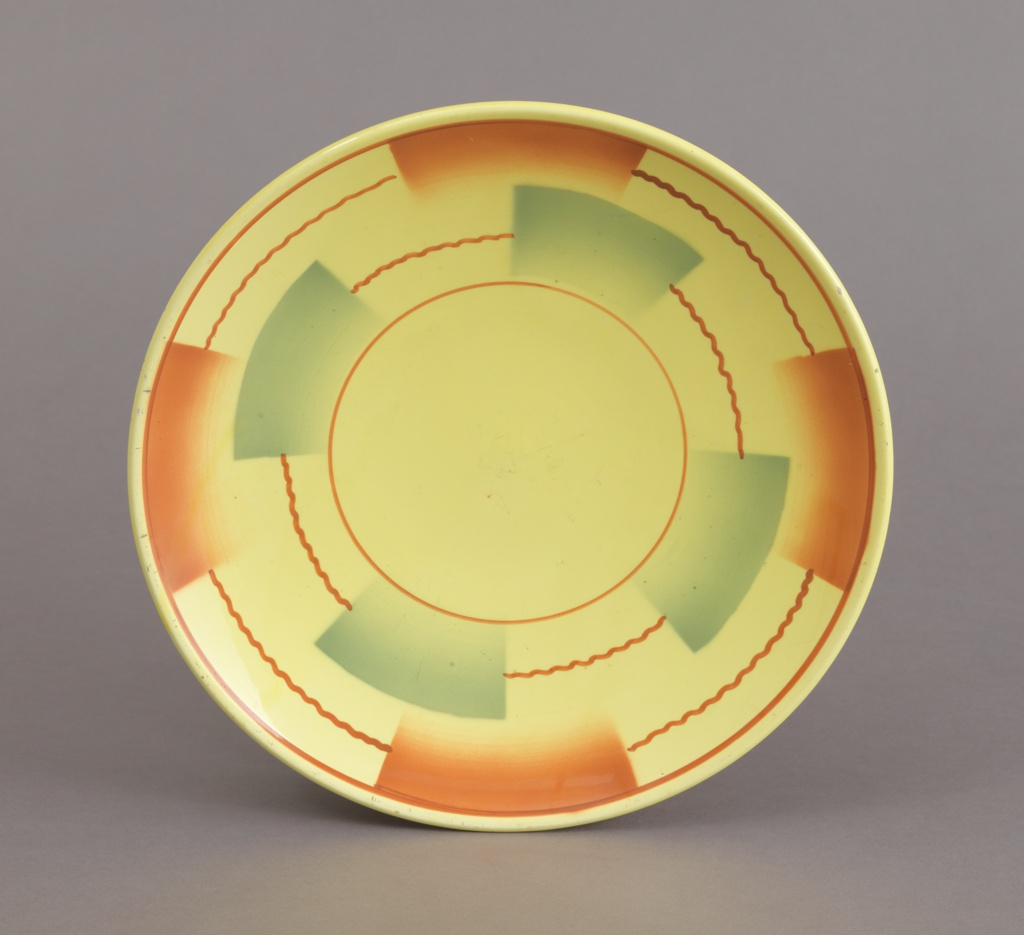 Circular dish with up-curved rim, circular foot ring; decoration of yellow ground with straight and wavy brown lines forming concentric circles broken by semi-rectangular airbrushed swatches of brown and green.