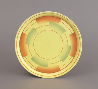 Circular plate with beveled rim. Yellow ground with straight and wavy brown lines forming concentric circles broken by semi-rectangular airbrushed swatches of brown and green.