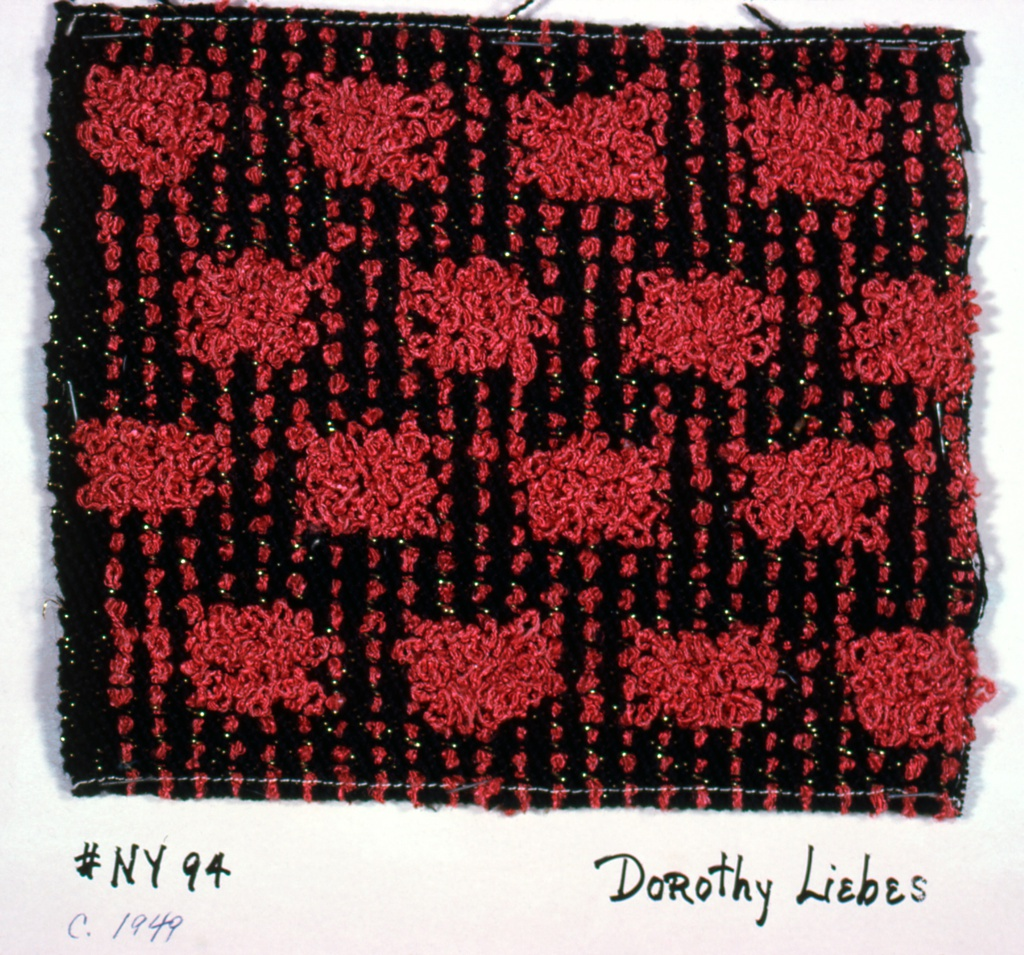 2/2 twill with geometric pattern of projecting loops made by supplementary warp.  Warp: black 3 ply string; supplementary warp of red bouclé. Weft: black 3 ply string paired with flat metallic gold.