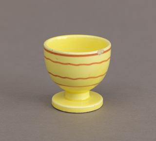 Circular bowl on short cylindrical stem with circular foot. Yellow ground throughout, the exterior decorated with a geometric pattern of two wavy brown lines bordered by two straight brown lines all running horizontally, broken by two airbrushed rectangles, one brown, one green.