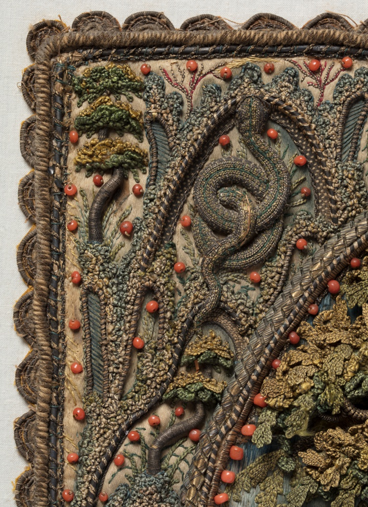 Small panel of embroidery in high relief of a tree in an oval with an elaborate framework.  The field is filled by an oak tree with dimensional leaves in shades of green. The trunk and branches are very dimensional, and are worked in silver metallic thread, now tarnished. At the base of the tree is a salamander, also in silver metallic thread. The background shows a landscape worked in pale silks with mountains and buildings, possibly a monastery. From the limbs of the tree hang crutches, a wax leg, and a censer.  The oval is surrounded by a row of coral beads and two rows of couched metal thread. The framework is embroidered with plant forms; in the two upper corners are coiled serpents, and in the two lower corners serpents emerge from cornucopias. The framework is accented accented throughout with coral beads and edged with a scalloped lace, probably added later.