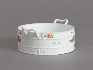 A white porcelain covered dish with a basket textured exterior. The covered dish has basket textured handles and an acorn knob.