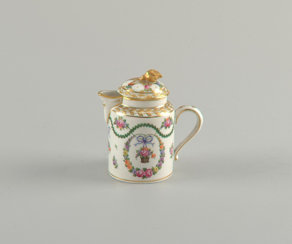 Cylindrical body and domed lid with gilded flower finial. Flower wreath encircling monogram. Short, wide spout.
