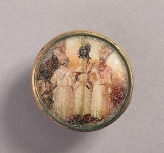 Button depicting scene of three women in the foreground and a seated man in the background in a partial landscape. The women are all wearing white dresses, turbans and scarves around their necks. The central figure wears a dark turban and has lighter skin than the other two.