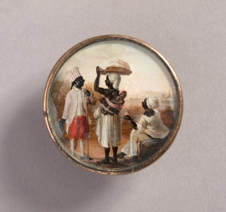 Button depicting scene of three figures before a seaport.  Man at left in striped turban and coat with red pants, holding a hat in one hand and a staff in the other. He speaks to a standing bare-breasted woman in a white skirt with a child tied to her back and carrying a package on her head. A second woman is seated on the right offering a piece of fruit to the child.