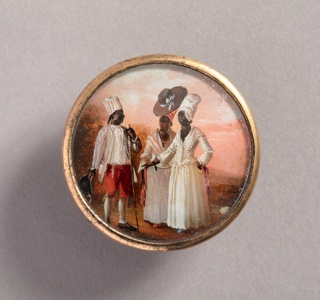 Button depicting scene with three figures in a pink-hued landscape. Man at left, wearing striped turban and red pants, doffs his hat for two women at right who wear white dresses and turbans; one of them women also wears a sunhat over her turban.