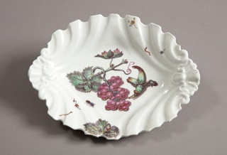 Dish with scalloped edges in ovoid; at center, bunch of grapes on stem with leaves and insects.
